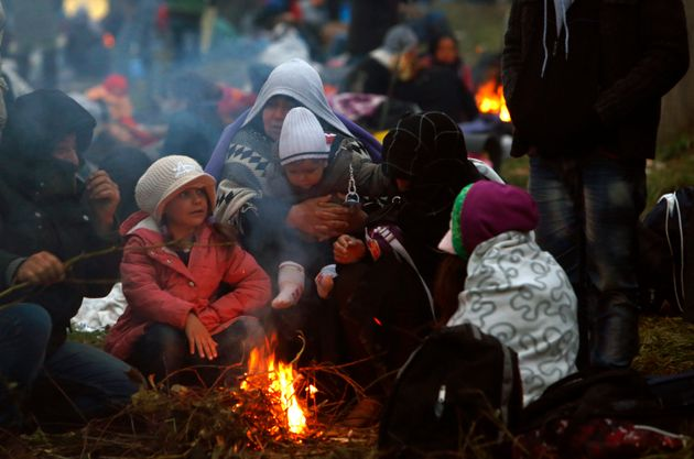 Families fleeing violence in Syria, here huddled around a fire at a makeshift camp in Slovenia in...