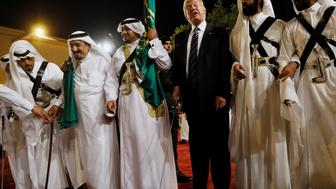 Saudi Arabia's King Salman bin Abdulaziz Al Saud (2nd L) welcomes U.S. President Donald Trump to dance with a sword during a welcome ceremony at Al Murabba Palace in Riyadh, Saudi Arabia May 20, 2017. REUTERS/Jonathan Ernst