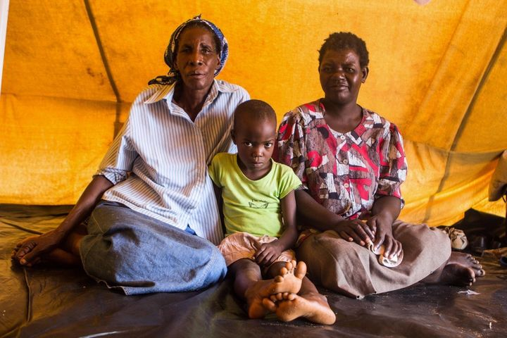 Jeselina Masuku, 67, (left) sits next to Sinokwethu Moyo, 7, and Thokozani Ncube, 48. Both Ncube and Masuku are anxious to le