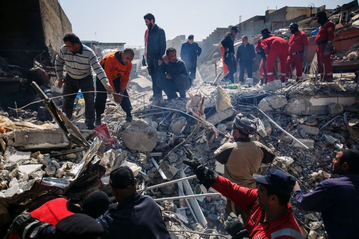Local residents help Iraqi civil defense force members recover corpses trapped in the rubble of a home destroyed by reported