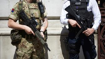 A British army soldier (L) and a police officer (R) secure an entrance to the British Foreign and Commonwealth Office (FCO) in central London on May 25, 2017, after Operation Temperer was put into force putting soldiers under police command on British streets in response to the May 22 terror attack at the Manchester Arena. Police said they arrested two men Thursday in the Manchester area in connection with the deadly bombing of an Ariana Grande pop concert, while a detained woman was released without charges. Britain has raised its terror alert to the maximum level and ordered troops to protect strategic sites after 22 people were killed in a suicide bomb attack on a Manchester pop concert. / AFP PHOTO / NIKLAS HALLE'N        (Photo credit should read NIKLAS HALLE'N/AFP/Getty Images)