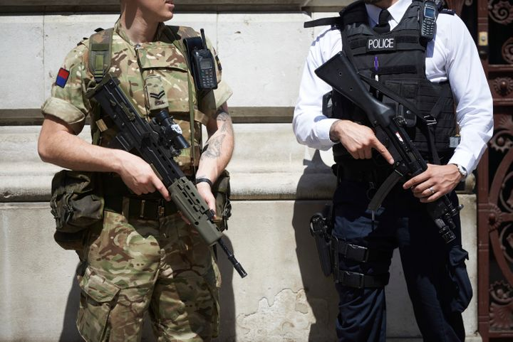 A British army soldier and police officer are stationed in London as Britain raises its terror alert following the attack in Manchester.