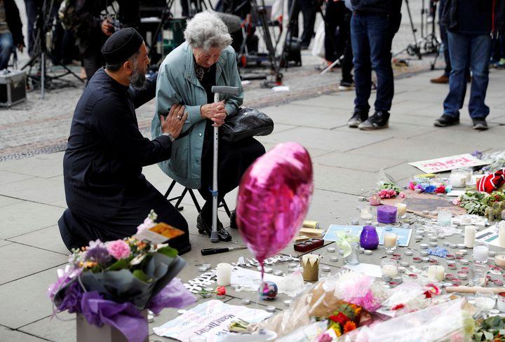 A Muslim man named Sadiq Patel comforts a Jewish woman named Renee Rachel Black next to floral tributes in Albert Square in M