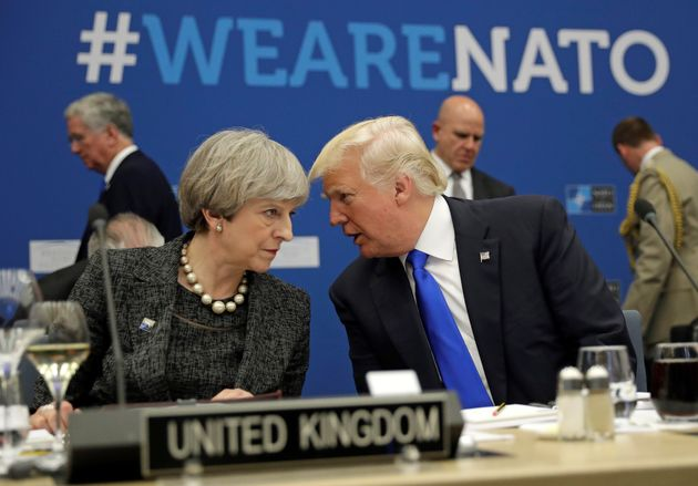 Trump was pictured speaking with Theresa May during a working dinner at Nato HQ in
