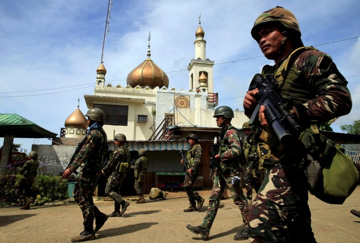 Government troops walk past a mosque before their assault with insurgents.