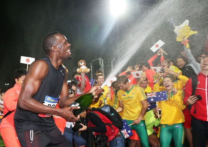 Usain Bolt of Usain Bolt's All-Star team sprays champagne on the teams after his team won the event during the Melbourne Nitr