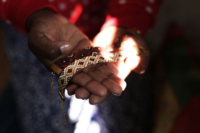 An artisan in rural Nepal presents her beaded bracelets.
