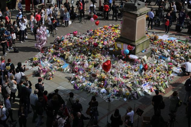 People gather around floral tributes to the victims of the Manchester attack at St Ann's Square on