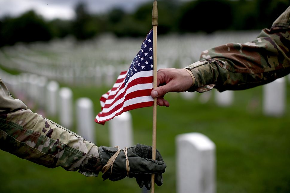 Two members of the 3rd U.S. Infantry Regiment place flags at the headstones of U.S. military personnel buried at Arlington Na