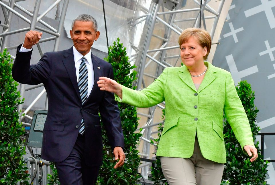 Barack Obama and Chancellor Angela Merkel wave as they arrive on stage during the Protestant Church Day event at the Brandenb