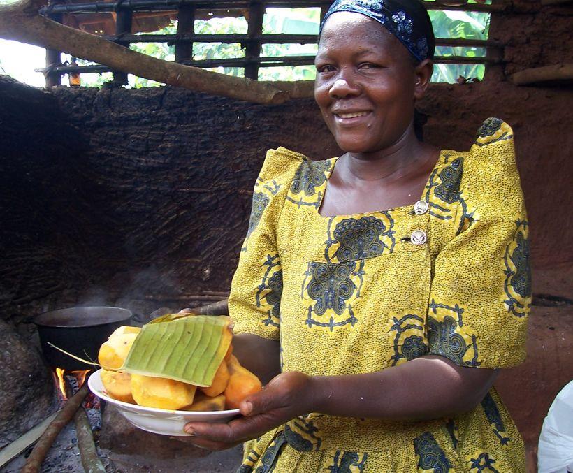 A Ugandan farmer with freshly steamed orange sweet potato, ready to eat