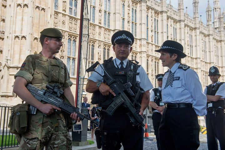 The threat level has been reduced from critical, back to severe, the Prime Minister said on Saturday, but soldiers will continue to police key sits until the end of the bank holiday weekend