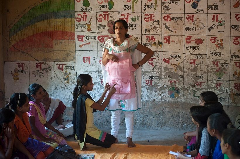 Kushboo Kumari (C sitting) ,15, gestures as she explains a diagram made on an apron worn by Manita (L),15, during an interact