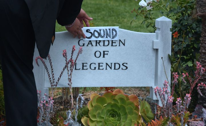Kanan Sanchez places a folded sheet of paper with the word 'Sound' over the stone at the Garden of Legends section of the Hol