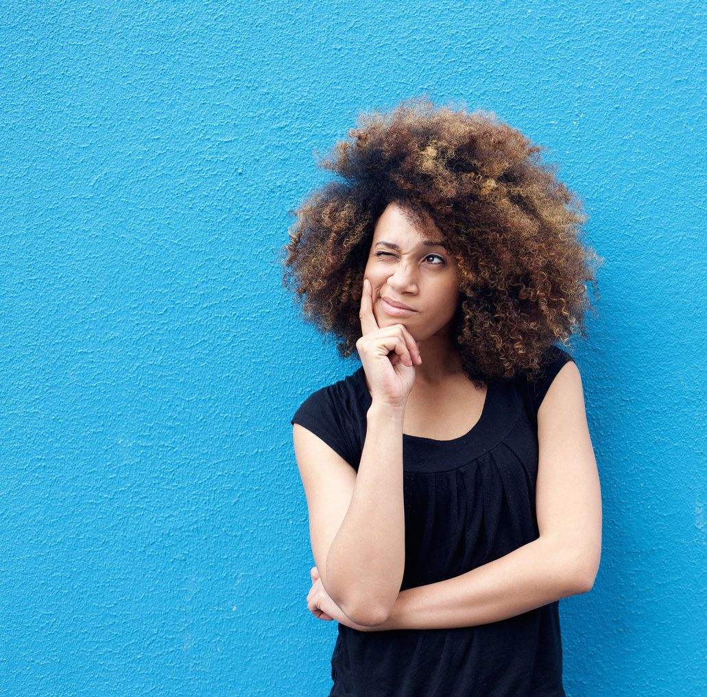 Portrait of young afro woman thinking against blue background
