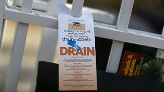 MIAMI BEACH, FL - APRIL 05:  A pamphlet educating people about mosquitos hangs on a fence as workers with Miami-Dade County mosquito control department inspect a neighborhood for any mosquitos or areas where they breed as the county works to eradicate mosquitos carrying the Zika virus on April 5, 2017 in Miami Beach, Florida. With peak mosquito breeding season just around the corner Miami-Dade county is far more prepared than they were in 2016 when federal health officials declared parts of Miami and Miami Beach the nation's first Zika transmission zones.  (Photo by Joe Raedle/Getty Images)