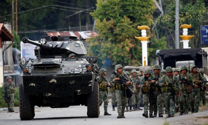 Members of Philippine Marines walk next to an armoured fighting vehicle (AFV) as they advance their position in Marawi City,