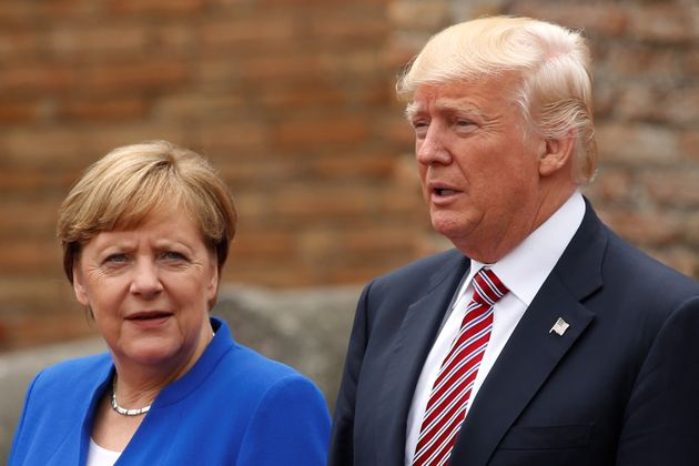 Donald Trump and Angela Merkel pose during a 'family photo' during the G7 summit in Taormina,