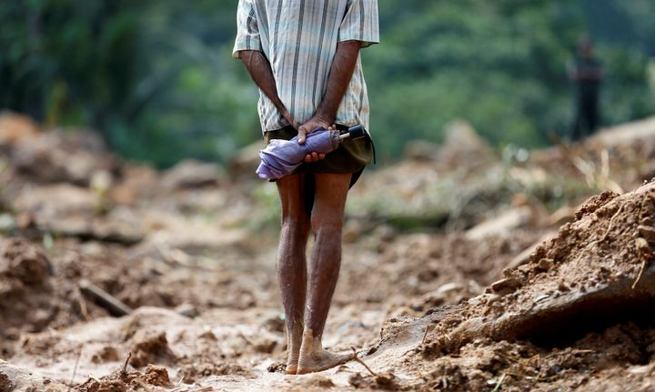 Torrential rains wreaked havoc in Sri Lanka in previous days. In this photo, a man looks at the site of a landslide in A
