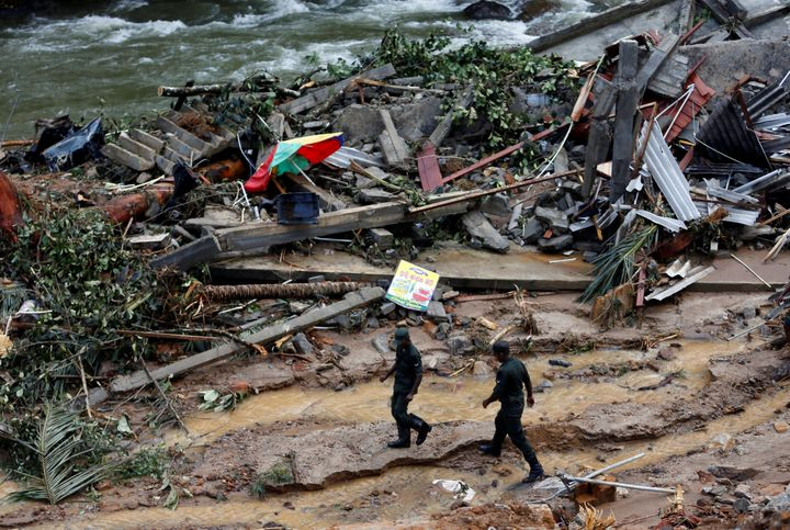 The rains caused both heavy flooding and enormous landslides. In this photo, Sri Lankan army soldiers walk past the debris of