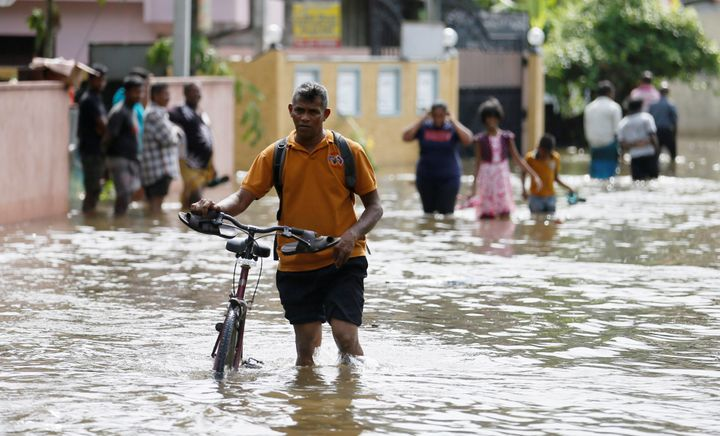 More than 150 people have lost their lives in the disaster. This photo shows a man pushing his bike through a flooded ro