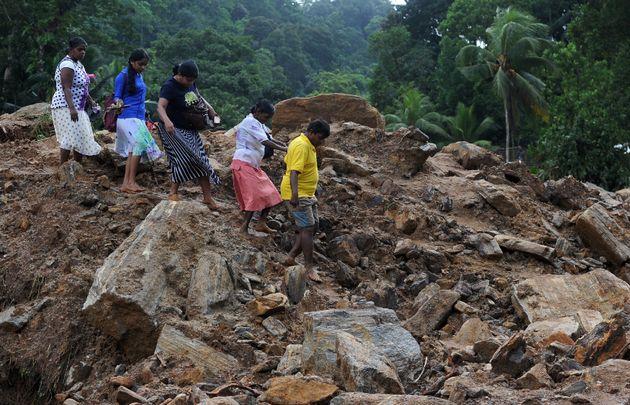 Sri Lankan villagers cross a landslide site in