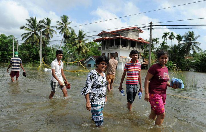 Sri Lankan residents walk through floodwaters in Kalutara.