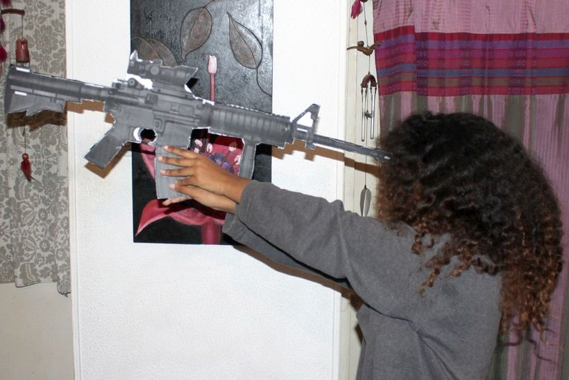 Toveet's sister holds a mock-up of the same rifle issued to Toveet, demonstrating that Toveet could not have reached the rifl
