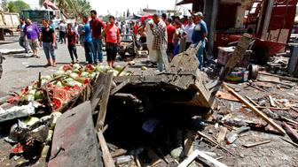 EDITORS NOTE: Graphic content / Iraqis gather at the site of a car bomb explosion near Baghdad's  Al-Shuhada Bridge on May 30, 2017 which killed at least five people and wounded 17, security and medical officials said.   There was no immediate claim of responsibility for the attack but the Islamic State group carries out frequent bombings targeting civilians in the Iraqi capital. The blast followed an overnight suicide bombing at a popular Baghdad ice cream shop that killed at least 21 people.  / AFP PHOTO / SABAH ARAR        (Photo credit should read SABAH ARAR/AFP/Getty Images)