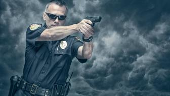 Policeman shooting his pistol. Arm Badge Create by me, Gold Chest Emblem Custom Ordered Generic. This stock image has a horizontal composition on a cloudy background.