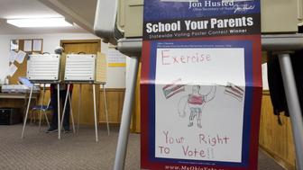 BUTLER TWP, OH - NOVEMBER 08: A winning student drawing from a statewide drawing contest, focusing on the issue of voting, is taped on the side of a voting booth as voters cast their ballots at the Butler Township Garage during Ohio's General Election on November 8, 2016 in Butler Township, Columbiana County, Ohio. This year, roughly 200 million Americans have registered to vote in this years general election between Republican presidential candidate Donald Trump and Democratic presidential candidate Hillary Clinton. (Photo by Ty Wright/Getty Images)