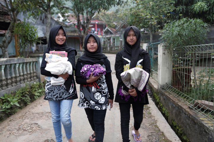 (L-R) Firdda Kurnia, Euis Siti Aisyah, and Widi Rahmawati, members of the metal hijab band Voice of Baceprot walk before they pray at a mosque in Garut, Indonesia, May 14, 2017.