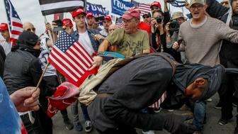 HUNTINGTON BEACH, CA - MARCH 25: A scuffle breaks out between Pro-Trump and Anti-Trump protestors during Make America Great Again March on March 25, 2017 in Huntington Beach. According to reports, an anti-Trump protester doused an event organizer with pepper spray prompting Trump supporters to retaliate. (Photo by Irfan Khan/Los Angeles Times via Getty Images)