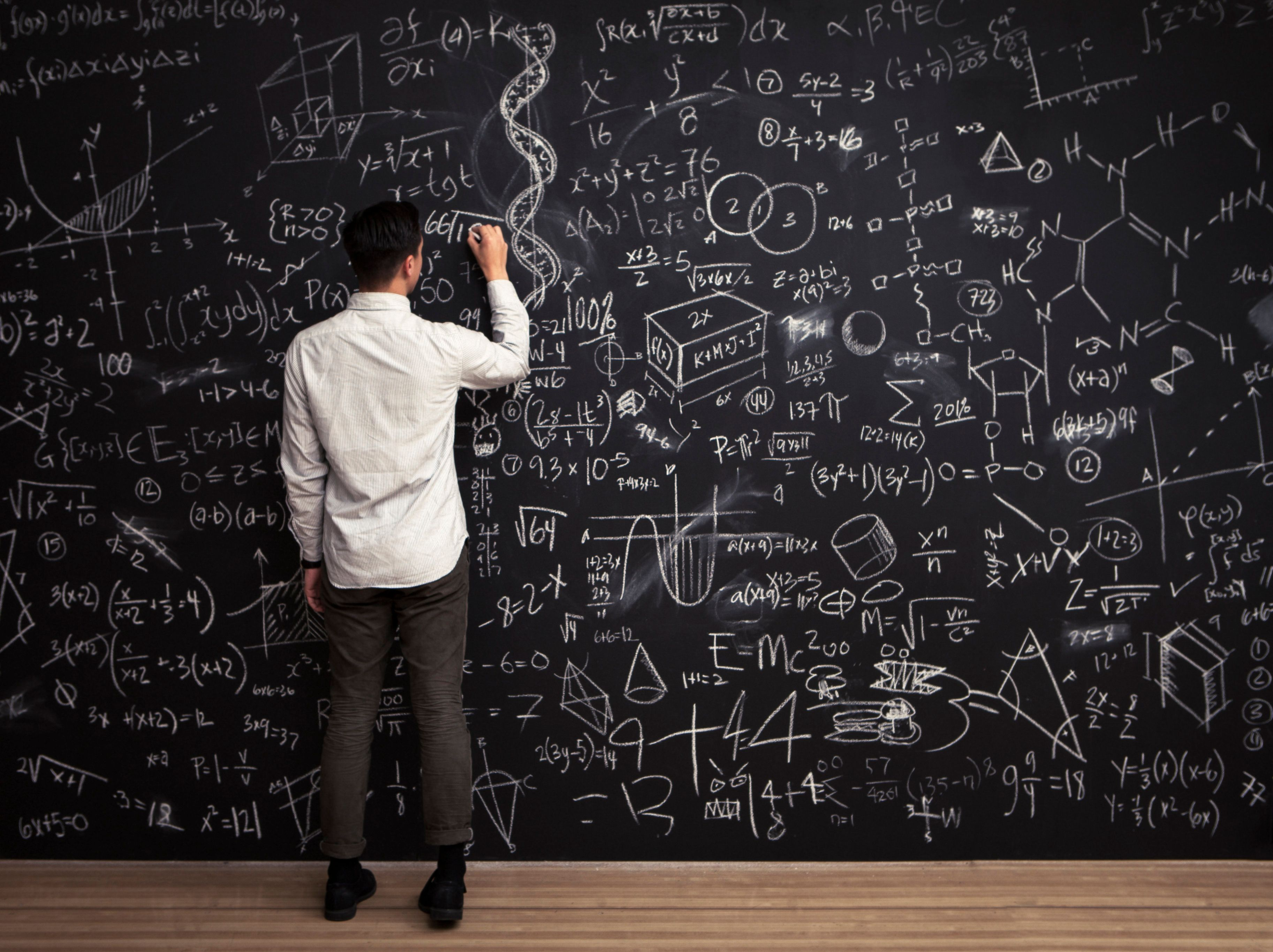 A young man writes on a chalkboard filled with mathematical equations, showing individuality, intelligence and creativity