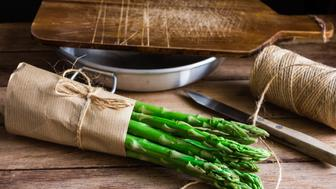 Bundle of fresh organic asparagus wrapped in craft paper on kitchen table, cutting board bowl knife, daylight, cozy atmosphere