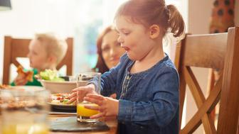 A 2 year old girl takes a big drink of orange juice halfway through her meal of pizza and salad and puts her glass down as she licks her lips. Her mum is in the background helping the little girls' young brother with his meal.