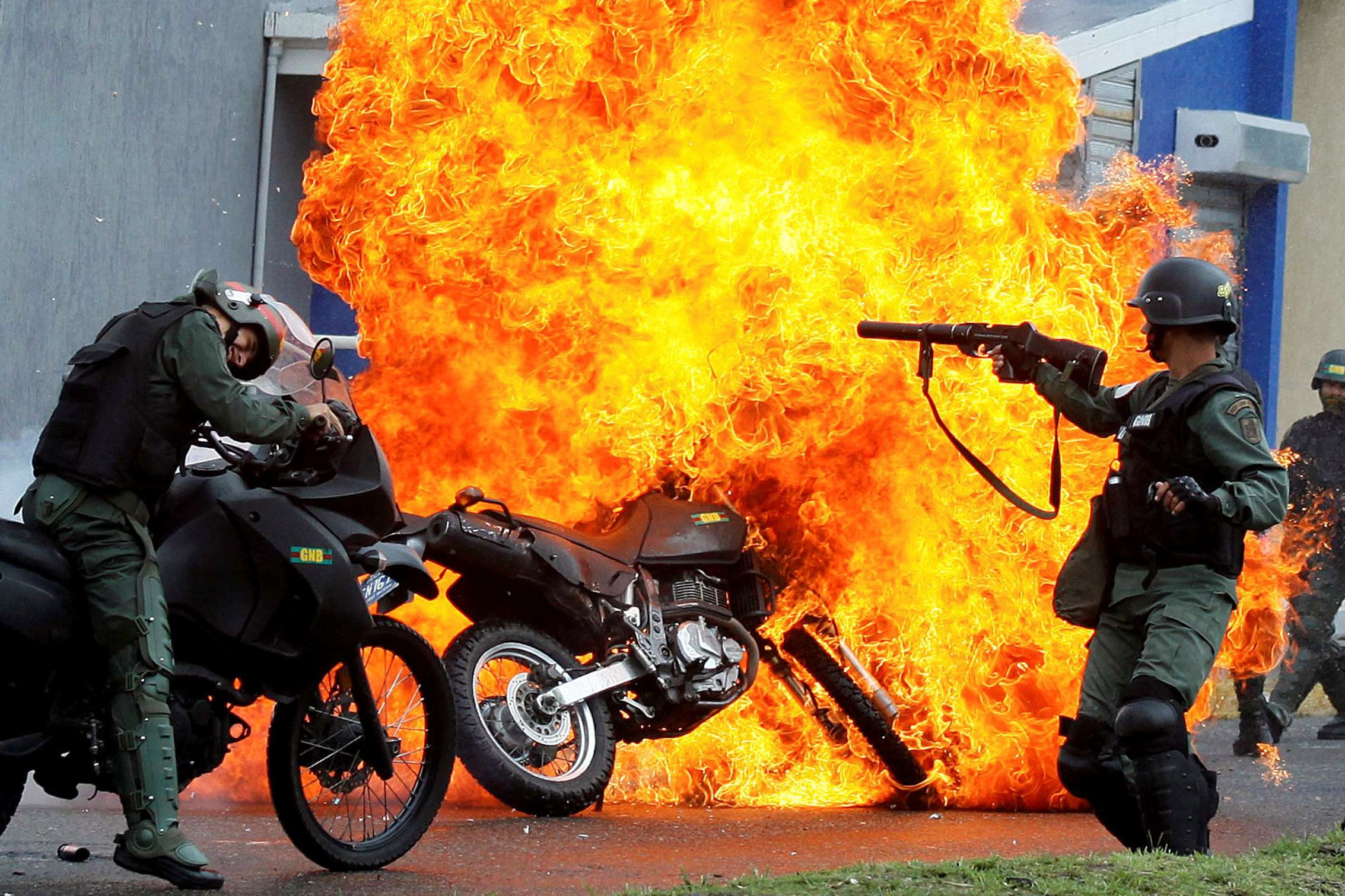 Riot security forces clash with demonstrators as a motorcycle is set on fire during a protest against Maduro. San Cristobal,