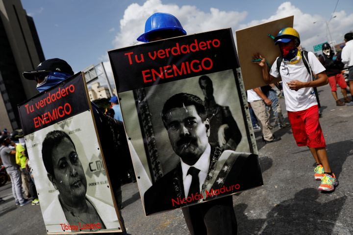 "Demonstrators carry signs of Maduro and National Electoral Council President Tibisay Lucena that reads "" your real enemy."" Ca"