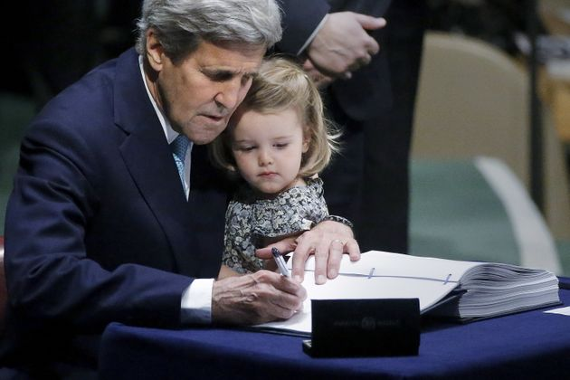 Then-Secretary of State John Kerry holds his 2-year-old granddaughter as he signs the Paris Agreement...