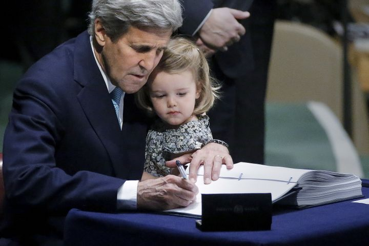 Then-Secretary of State John Kerry holds his 2-year-old granddaughter as he signs the Paris Agreement on climate change at Un