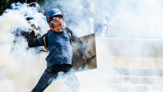 TOPSHOT - Opposition activists and riot police clash during a demonstration against President Nicolas Maduro's government in Caracas on May 29, 2017. Demonstrations that got underway in late March have claimed the lives of 59 people, as opposition leaders seek to ramp up pressure on Venezuela's leftist president, whose already-low popularity has cratered amid ongoing shortages of food and medicines, among other economic woes. / AFP PHOTO / LUIS ROBAYO        (Photo credit should read LUIS ROBAYO/AFP/Getty Images)