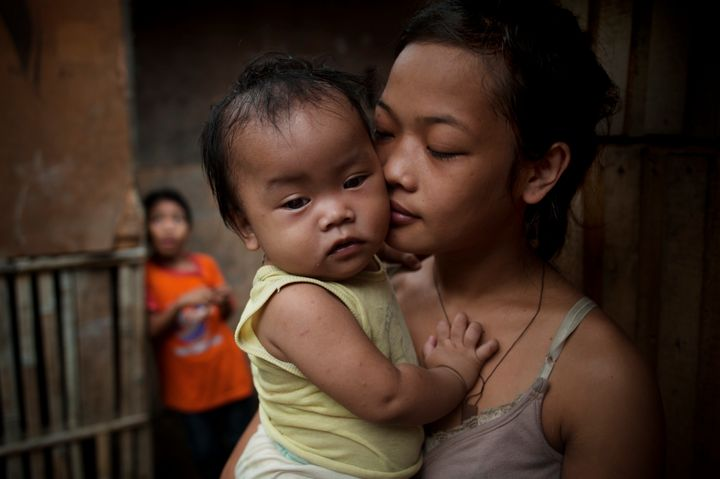 A 14-year-old girl carries her 10-month-old baby in Cagayan de Oro in the Philippines, where abortion is illegal and the Cath