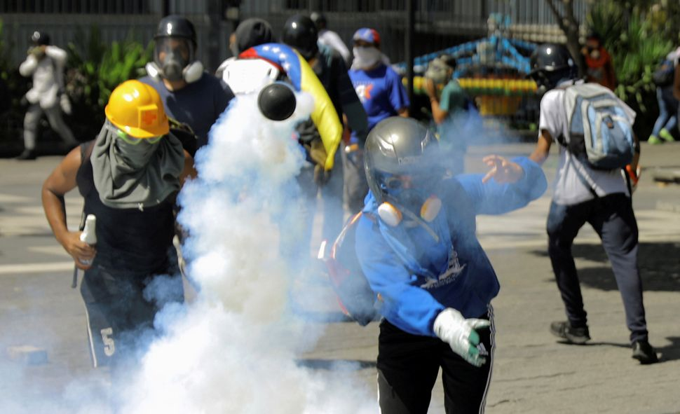 A demonstrator throws a tear gas canister during clashes with riot security forces at a protest against Venezuelan President