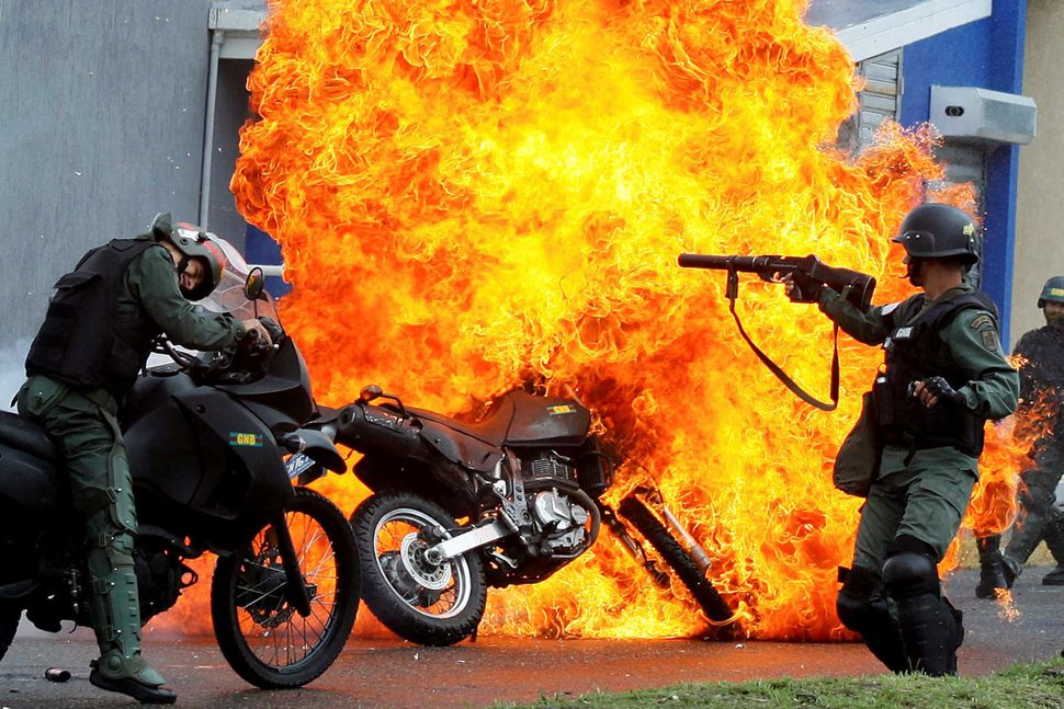 Riot security forces clash with demonstrators as a motorcycle is set on fire in San Cristobal, Venezuela, on May 29.