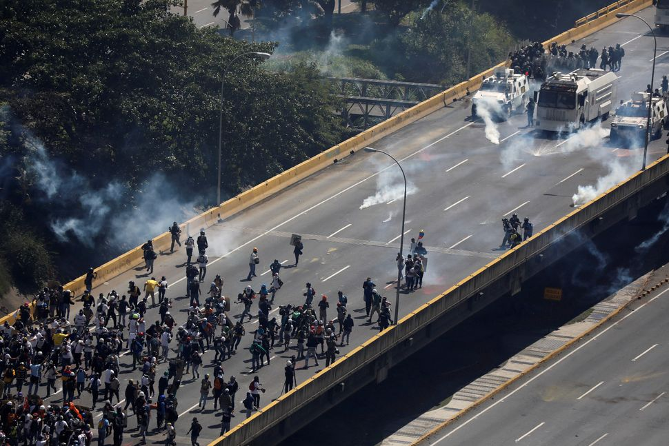 Demonstrators face off against riot security forces at a march to the state ombudsman's office in Caracas, Venezuela, on May