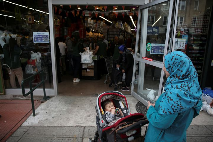 A Muslim American woman wearing hijab awaits outside the Balady halal supermarket with a child ahead of the first day of Rama