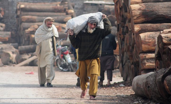 An elderly Afghan refugee carries a sack in a slum neighborhood for refugees in Islamabad, Pakistan, on Feb. 8. Pakistan