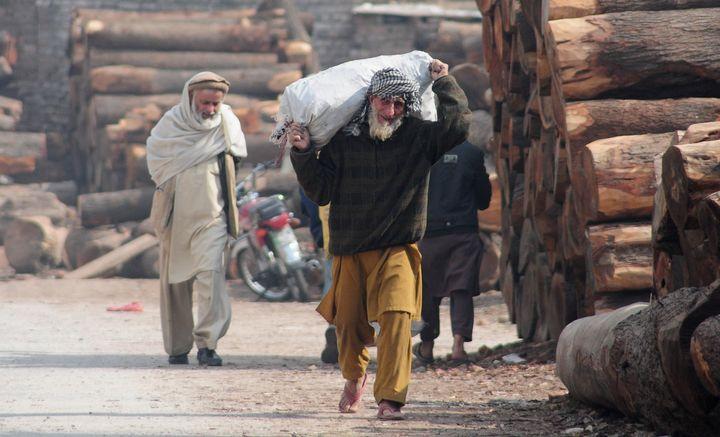 An elderly Afghan refugee carries a sack ina slum neighborhood for refugees in Islamabad, Pakistan, on Feb. 8. Pakistan
