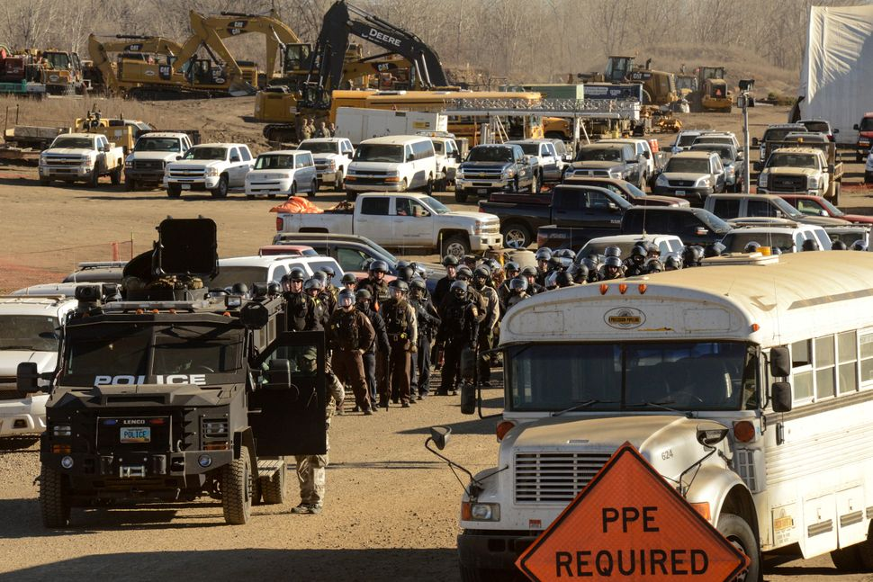 Police stand guard in a Dakota Access pipeline construction facility.