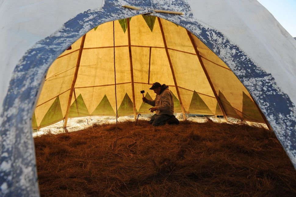 Steve Tamayo drives in stakes to his tipi in an encampment.